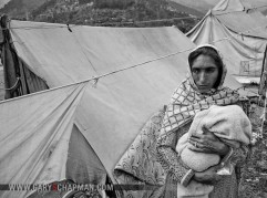 Pakistani woman and child living in a tent city after the earthquake destroyed her home-greyscale.