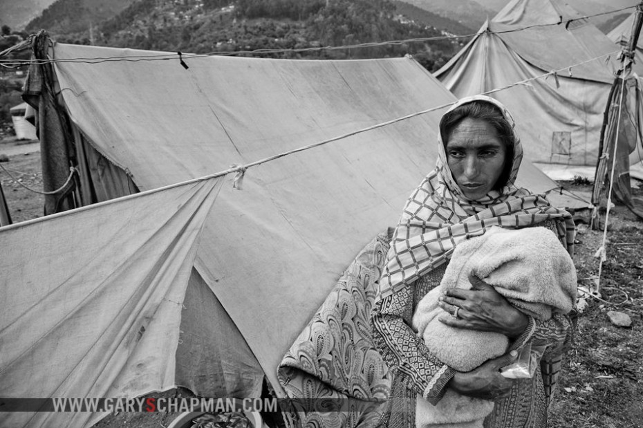 Pakistani woman and child living in a tent city after the earthquake destroyed her home.